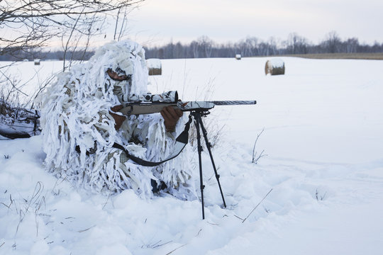 Varmint Hunter In Ghillie Snow Suit With Rifle On Bipod in winter