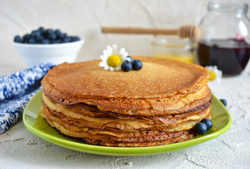 pancakes with blueberries and honey on a concrete background