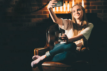 Girl in a cozy dark room holding a phone. Blonde and warm lamp light