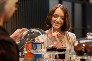 happy woman choosing cakes at vegan cafe