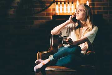 Girl in a cozy dark room is sitting on a chair and talking on the phone. Blonde and warm lamp light
