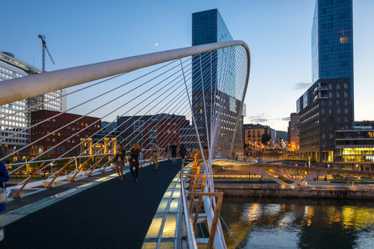 View to the Plaza de la Convivencia with the famous bridge Puente Zubizuri, The white bridge, also named Campo Volantin Bridge, is a tied arch footbridge across the Nervion River in Bilbao, Spain