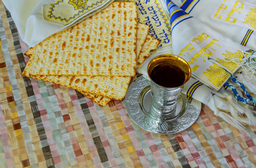 Jewish traditional Passover unleavened bread and a wine cup with the text of the traditional wine blessing