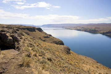 Washington state landscape with Columbia river and canyon. Geological formation with rocky shores with sparse vegetation and bright water reflecting the blue sky.