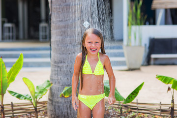 Beautiful happy little girl in a yellow bathing suit under a shower on the beach in a tropical garden