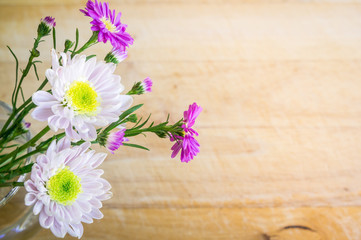 Pink and white flowers on  wooden background. Flat lay. Top view with copy space. Selective focus.