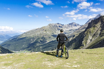 Mountain biker enjoys his view, standing on a alp summits rim