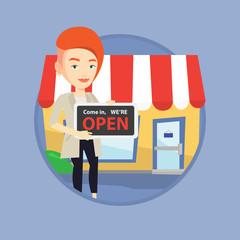 Female shop owner holding open signboard.