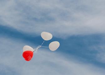 Rote und weiße Luftballons zur Hochzeit am blau weißen Himmel