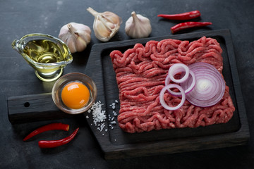 Black wooden serving tray with raw beef mincemeat and seasonings