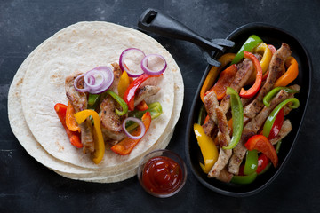 Fajitas with colorful bell peppers and pork meat, top view, studio shot