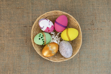 Easter egg design in round rattan basket on hessian background
