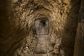 Inside abandoned gold mine tunnel or shaft in the Nevada desert.  There are ore cart tracks on the floor.  Shallow Depth of Field with focus about half way down the shaft.
