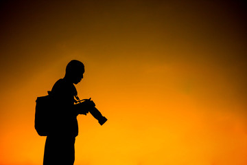 silhouette of a photographer who shoots a sunset.