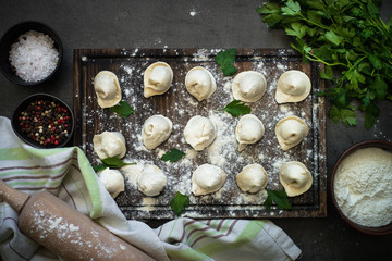 Traditional homemade pelmeni or dumpling at cutting board.