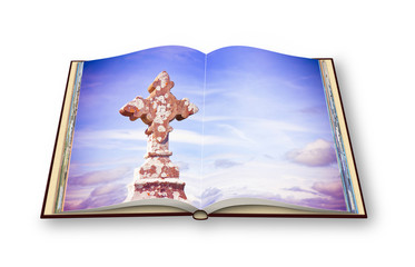 Opened photobook isolated on white background with celtic carved stone cross (Ireland)