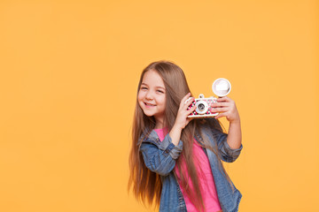 little girl photographer smiling and holding a retro camera