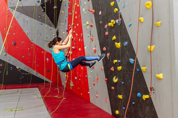 Happy sporty woman with climbing equipment hanging on a rope at indoor rock-climbing artificial wall