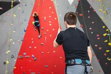 Coach climber belay amateur athlete on a high climbing wall.