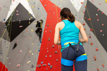 Sport woman at the rock climbing wall at the gym looking at her friend on the track
