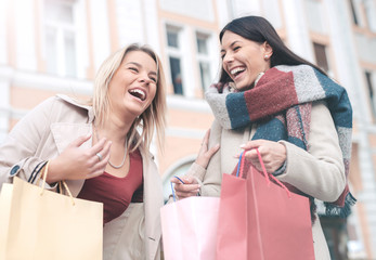 Young women shopping together. Consumerism, shopping, lifestyle concept