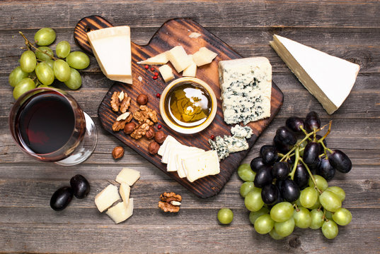 Grapes, red wine, cheeses, honey and nuts over rustic weathered wood. Top view.