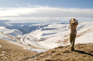 Beautiful blonde girl with a camera to take pictures of Caucasian mountains