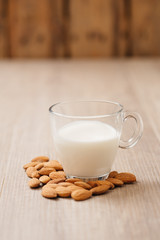 Glass of almond milk with almonds on wooden table