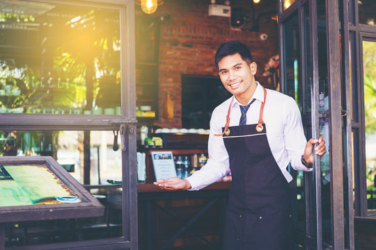 handsome man waiter open the door and warm welcome to you