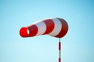 Horizontally flying windsock (wind vane) due to high wind. Blue sky in the background. Success concept.