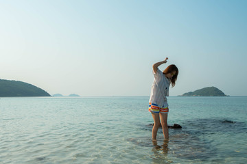 Happy woman standing arms outstretched on the beach at Sea