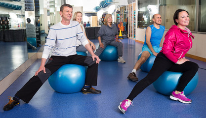 elderly exercise with gymnastic balls in modern gym