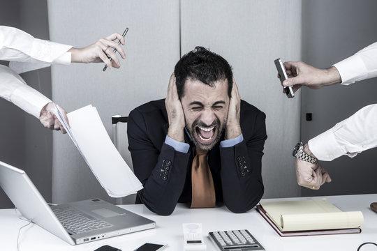 manager al centro è disperato mentre tante mani gli danno compiti. Tiene le mani nelle orecchi e urla.