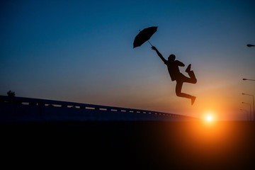 Silhouette men jumping umbrella on street the sunset.