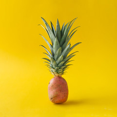 Potato with pineapple leaves on bright yellow background. Minimal fruit concept.