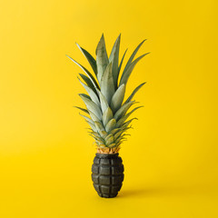Grenade bomb with pineapple leaves on bright yellow background. Minimal fruit concept.