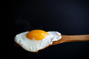 Foto auf Acrylglas Eier Fried egg with a wooden spoon
