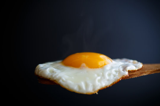 Fried egg with a wooden spoon