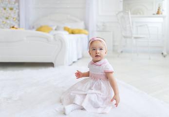 Sweet baby girl sitting on the floor in white bedroom