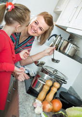 Little girl and mother at home kitchen.