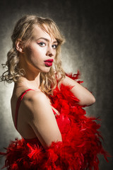 Beautiful young blond woman dressed in red sexy dress and red feather boa scarf, studio shut on black background