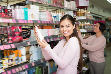 Young woman picking cream from shelf
