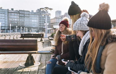 Spain, Gijon, four friends using their cell phones outdoors