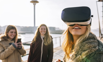 Teenage girl using wearing VR glasses while her friend watching her
