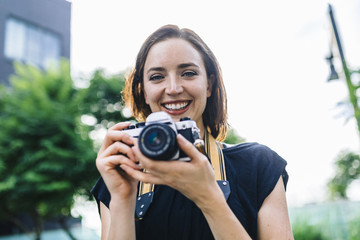 Portrait of smiling woman with camera