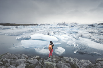 Iceland, view of Joekulsarlon, glacial river lagoon with man standing in the foreground