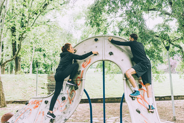 Fit couple climbing a wall unite outdoor in a park - fitness, wellness, training concept