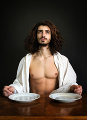 photo guy with long curly hair white drapery and two empty plates looking up