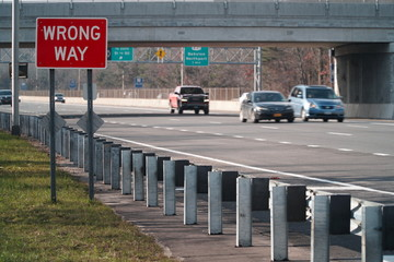 Wrong Way caution safety sign posted along a major interstate highway facing the opposite direction of traffic to avoid car vehicle collision accidents