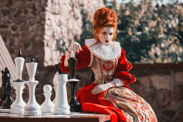 The Red Queen is playing chess. Red-haired woman in a chic vintage dress. Fashion Photo Wall mural